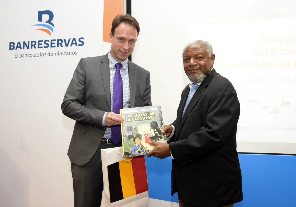 Patrick Van Gheel, embajador de Bélgica en RD, entrega un ejemplar de comics belgas a Juan Freddy Armando, director del Centro Cultural Banreservas.