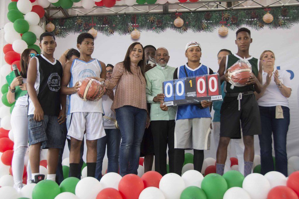 La presidente del Voluntariado Banreservas, Jacqueline Ortiz de Lizardo, entrega un donativo a jóvenes deportistas de comunidades cercanas al rio Ozama.