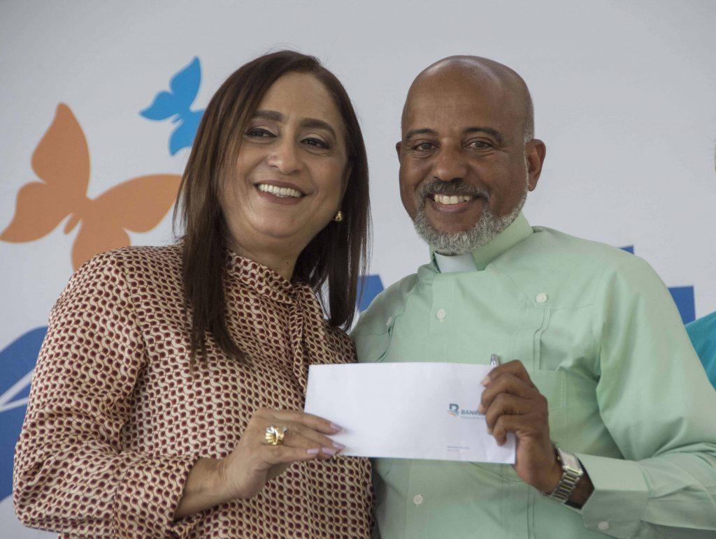 La presidente del Voluntariado Banreservas, Jacqueline Ortiz de Lizardo, entrega un donativo al padre Manuel Ruiz, para dar continuidad a su labor solidaria en los barrios de las riberas del Ozama.